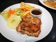 Kurczaka stek w białym talerzu na czarnym stole fotografia stock