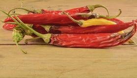 Kurczyć się i lejni chili pieprze na białym drewnianym tle Przegnili chili pieprze Zdjęcia Stock