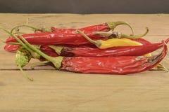 Kurczyć się i lejni chili pieprze na białym drewnianym tle Przegnili chili pieprze Zdjęcie Royalty Free