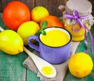 kurde Crème anglaise de citron et citrons, oranges et menthe frais sur la vieille table en bois Image stock