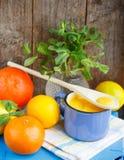 kurde Crème anglaise de citron et citrons, oranges et menthe frais sur la vieille table en bois Photos stock