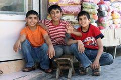 Kurdish boys in Urfa in Turkey. Smiling Kurdish boys sit in front of a textile stall in the Urfa (Sanliurfa) bazaar in south eastern Turkey Royalty Free Stock Photography