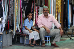 A Kurdish man and his son at Urfa in Turkey. A Kurdish man and his son sit in front of their belt store in the Urfa (Sanliurfa) bazaar in south eastern Turkey Royalty Free Stock Photography