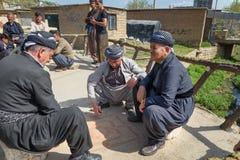 Kurdish men playing traditional game with small stones on the streets in Darreh Tafi village near Zarivar lake, Iran royalty free stock photos