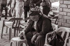 Kurdish old man. Erbil, Iraq - March 7, 2016: Old Kurdish man drinking hot tea in coffee  shop in Iraq Royalty Free Stock Photo
