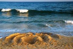 Kurenda projekty w piasku z fala obrazy stock