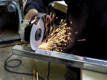 Kurenda zobaczył piłowanie z iskrami Mężczyzna pracuje z elektrycznym ostrzarza narzędziem na stalowej strukturze w fabryce, iski zdjęcia stock