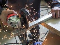 Kurenda zobaczył piłowanie z iskrami Mężczyzna pracuje z elektrycznym ostrzarza narzędziem na stalowej strukturze w fabryce, iski fotografia stock