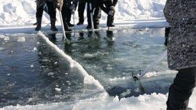 Kurgan, RUSIA - 14 de febrero de 2016: Los hombres adultos utilizan las sierras especiales para cortar el hielo en la navegación  metrajes