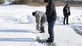 Kurgan, RUSLAND - Februari 14, 2016: Twee volwassen mensen gebruiken speciale zagen voor scherp ijs op het extreme varen op stock videobeelden