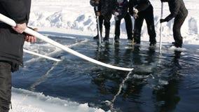 Kurgan, RUSSIA - 14 febbraio 2016: Gli uomini adulti utilizzano le seghe speciali per il taglio del ghiaccio sulla navigazione es video d archivio