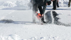 KURGAN, RUSSIA - 14 febbraio 2016: Un uomo usa uno speciale ha visto per tagliare il ghiaccio per la navigazione estrema sul lago archivi video