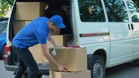 Kurier bierze pudełka out od doręczeniowego samochodu dostawczego, poruszająca firma, towarowy transport zbiory