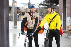 Kurier-Delivery Men With-Fahrräder, die jedes betrachten Stockbilder