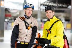 Kurier-Delivery Men With-Fahrräder unter Verwendung Digital Stockbild