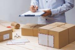 Kurier, der bei Tisch Anmerkungen im Lieferungsempfang unter Paketen macht Lizenzfreie Stockfotos