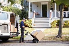 Kurier Knocking On Door des Hauses, zum des Pakets zu liefern lizenzfreie stockfotos