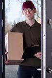 Kurier mit der Bestellung, die in der Tür steht stockbilder