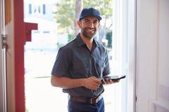 Kurier Standing At Front Door With Digital Tablet Lizenzfreie Stockfotos