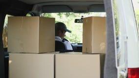 Kurier und Auto voll von Paketen stock footage