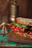 Kuriertes Fleischsandwich mit gesätem Brot auf altem Holztisch Stockfoto