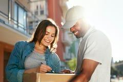 KurierZustelldienst Mann, der Paket an Frau liefert lizenzfreie stockfotos