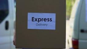 Kurir för uttrycklig leverans i enhetlig hållande kartonginternationalsändning arkivfilmer