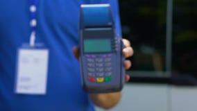 Kurir i likformign som ger terminalen för elektronisk betalning till klienten, lätt bankrörelse arkivfilmer