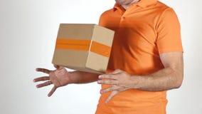 Kurir i orange likformig som kastar en småpaket Ljus - grå backround, toppet ultrarapidcloseupskott lager videofilmer