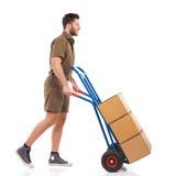 Kurir som går med en leveransvagn Arkivfoton