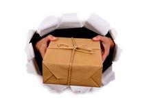 Kuriren eller brevbäraren räcker att leverera eller att ge småpaketet till och med sönderriven vitbokbakgrund Royaltyfria Foton