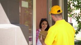 Kuriren i gul likformig levererar pizzaaskar till kvinnan på dörröppningen lager videofilmer