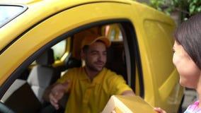 Kuriren i gul skåpbil ger packen till den kvinnliga kunden stock video