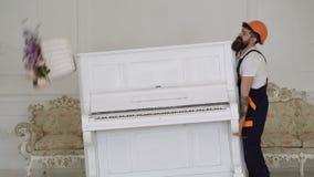 Kuriren levererar möblemang i fall att av flyttningen ut Begrepp f?r kurirservice Laddaren flyttar pianoinstrumentet Skada till l lager videofilmer
