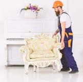 Kuriren levererar m?blemang i fall att av flyttar sig ut, f?rflyttning Mannen med sk?gget, arbetaren i overaller och hj?lmen lyft arkivbild