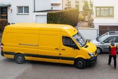 Kuriren skriver in DHL den gula leveransskåpbilen, når den har levererat royaltyfri fotografi