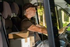 Kurirman som kör lastbilen som levererar packen Arkivbild