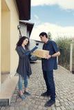 KurirWoman Receiving Boxes hem- leverans Royaltyfri Foto