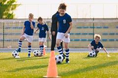 Kurs f?r fysisk utbildning f?r fotboll Barn som utbildar fotboll p? skolaf?lt royaltyfria foton