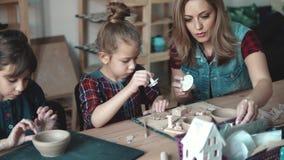 Kurs i krukmakeri barn som gjutas entusiastiskt från lera Mamman och två döttrar är förlovade i gemensam kreativitet stock video