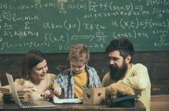 Kurs i teckning Det lilla barnet lär teckningen på papper Kvinnan och mannen ger pojkekurs i teckning Jag gillar att dra royaltyfri bild