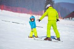 Kurs på skidåkningskolan: instruktör som undervisar den lilla skidåkaren Royaltyfria Foton
