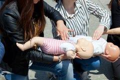 Kursen av första hjälpen med behandla som ett barn - dockan Arkivbild