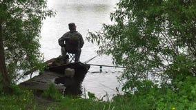 Kursk, Rusland - Mei 28, 2017: een visser in de vorm van een wacht zit op de kust en vangt een vis stock footage