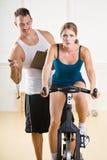 Kursleiterzeitbegrenzungfrau auf stationärem Fahrrad Lizenzfreies Stockfoto