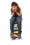 Kursteilnehmer, der auf einem Stapel der Bücher sitzt Lizenzfreie Stockfotografie