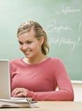 Kursteilnehmer, der auf Laptop im Klassenzimmer schreibt Lizenzfreie Stockfotos