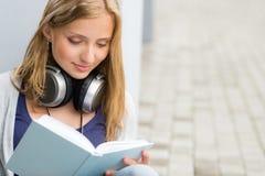 Kursteilnehmer, der ein Buch außerhalb der Universität liest Stockbild