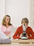 Kursteilnehmer, der Mikroskop im Klassenzimmer untersucht stockfotos