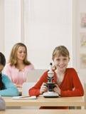 Kursteilnehmer, der Mikroskop im Klassenzimmer untersucht stockbild